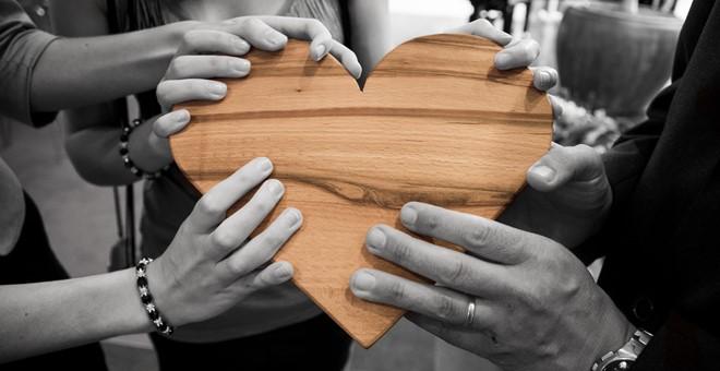 Händer som håller i ett hjärta av trä